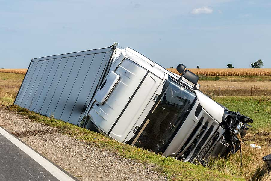 The truck lies in a side ditch after the road accident