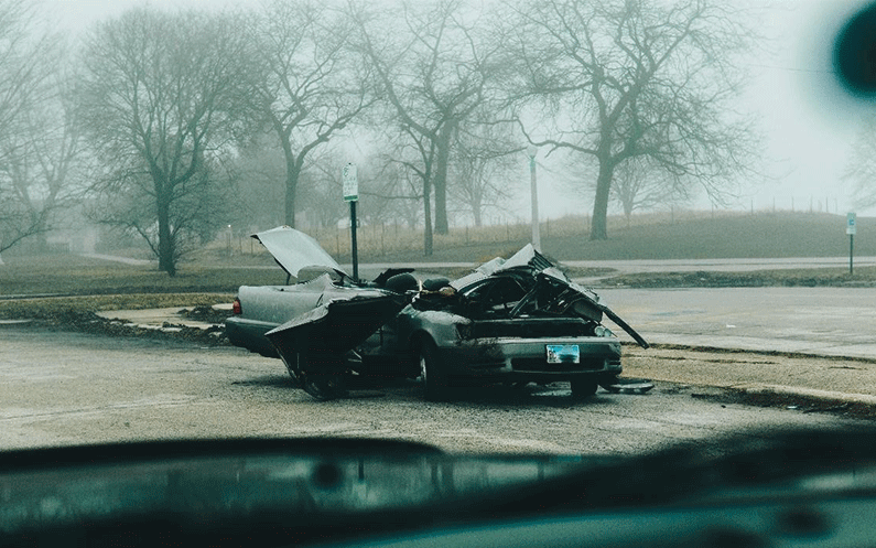 A wrecked and crashed car on a foggy road